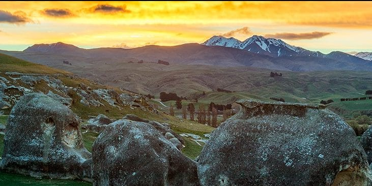 oamaru accommodation - sunset with green rolling hills and two mountain peaks in the distance